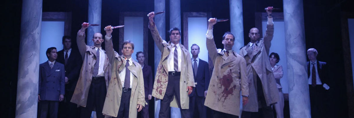 Five men in bloodied trenchcoats raise knives in the air.