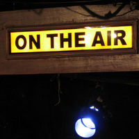 A sign reading ON THE AIR lit up above the Strawdog stage.