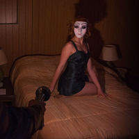 A masked woman sits on a bed in a hotel room lit by flashlight.
